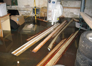 A severely flooding basement in Amherstburg, with lumber and personal items floating in a foot of water